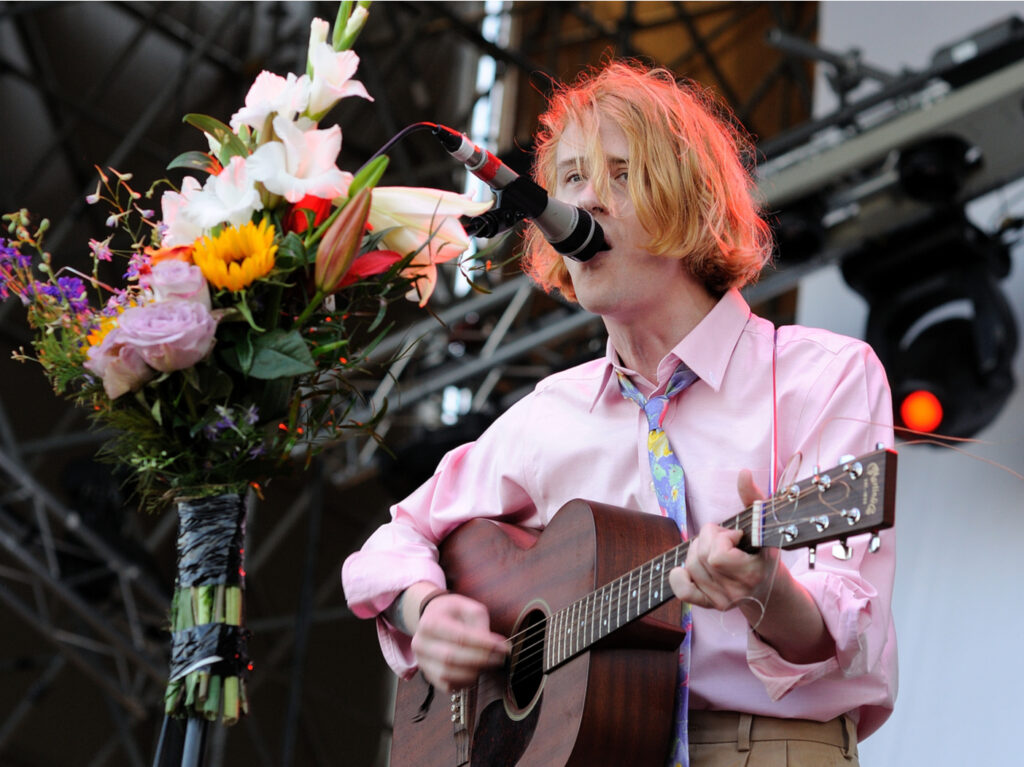 Christopher Owens holds a guitar and sings into a microphone