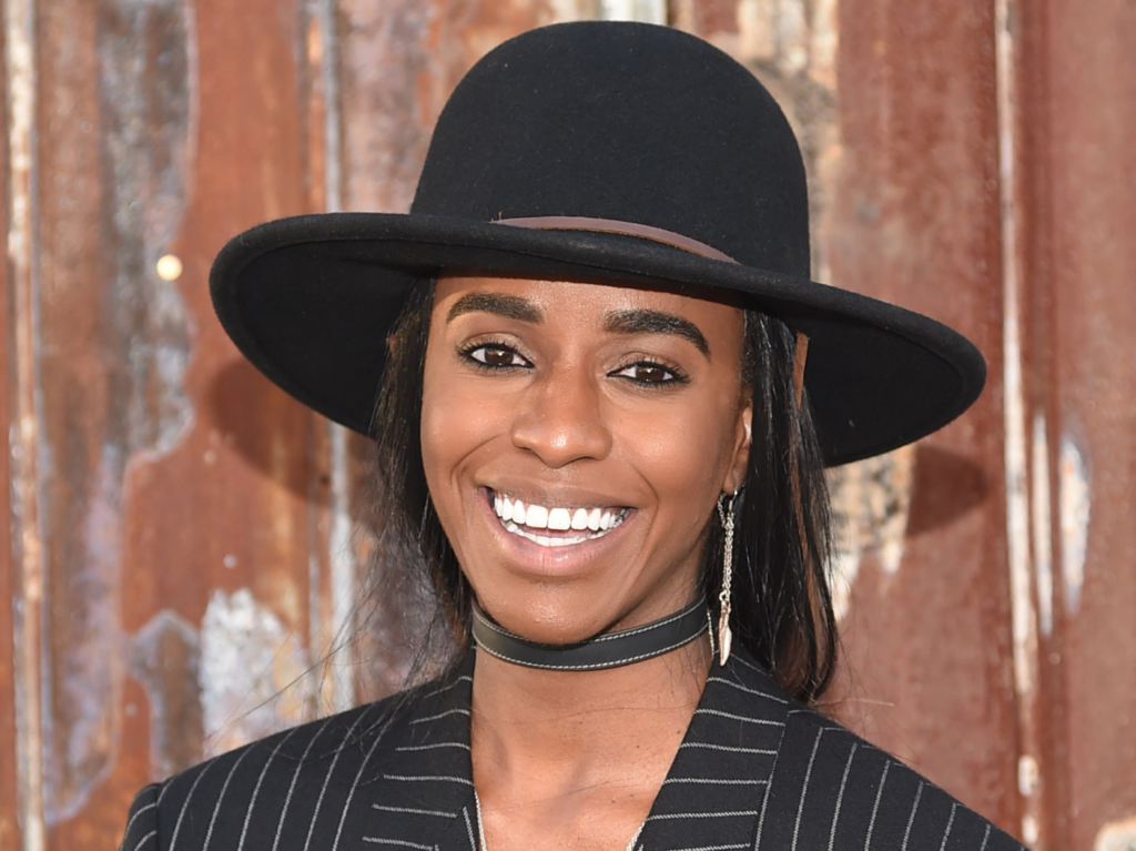 Angel Haze is wearing a black prospector hat and pinstriped top