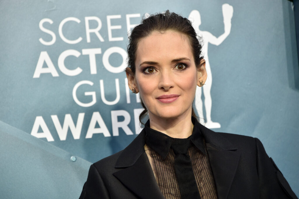 Winona Ryder is wearing a black suit jacket and lace shirt underneath