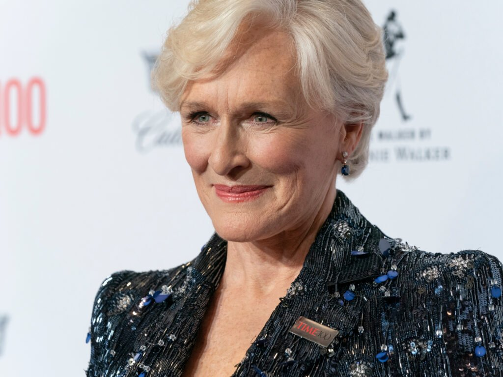 Glenn Close smiles at the camera with a unique jacket