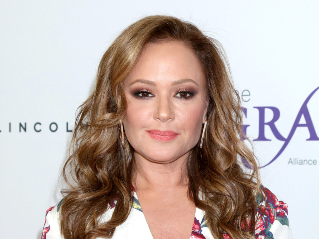 Leah Remini wearing a floral white dress with her hair down