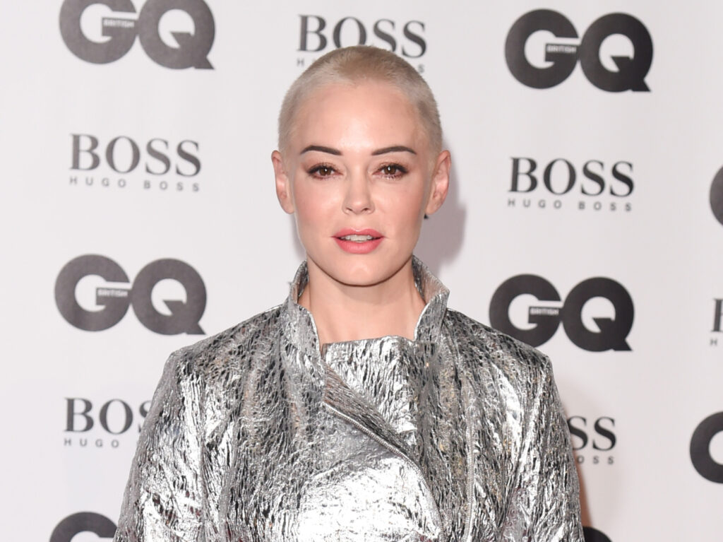Rose McGowan with a shaved head and modest silver outfit