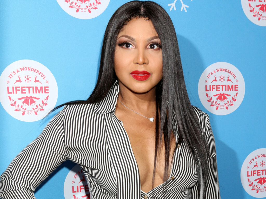 Toni Braxton stands on the red carpet in a black and white pinstripe top