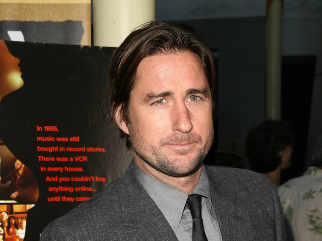 Luke Wilson looks at the camera stoically in a grey suit