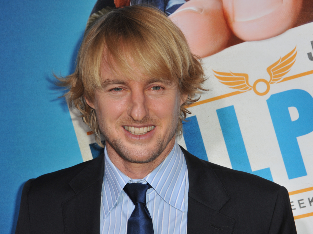 Owen Wilson in a black jacket and blue collared shirt.