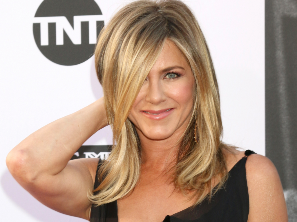 Jennifer Aniston gives the camera a demur smile while messing with her hair