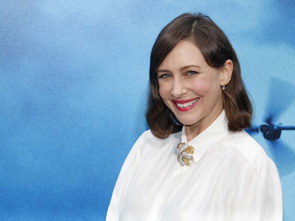 Vera Farmiga wears a collared white shirt while smiling at the camera