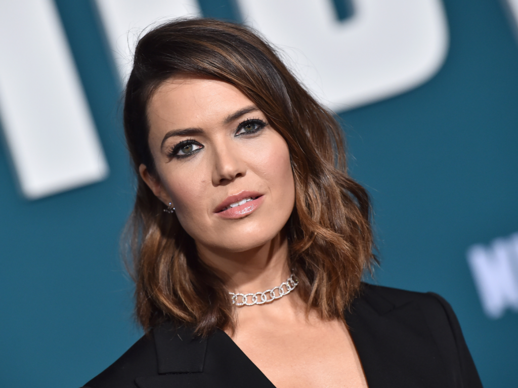 Mandy Moore poses with smokey eye makeup and a black dress
