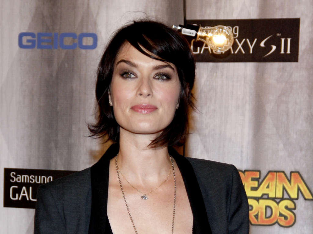 Lena Headey staring past the camera in a plunging neckline dress with short cropped hair