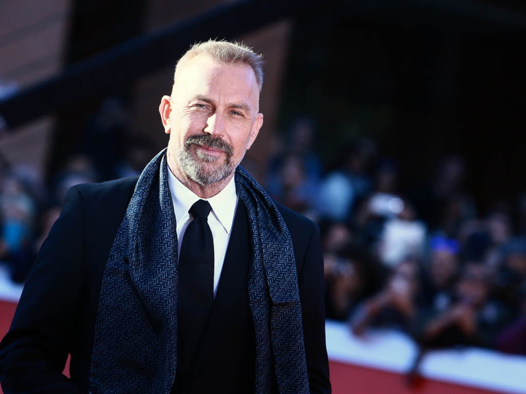 Kevin Costner wears a dark jacket and scarf on the red carpet