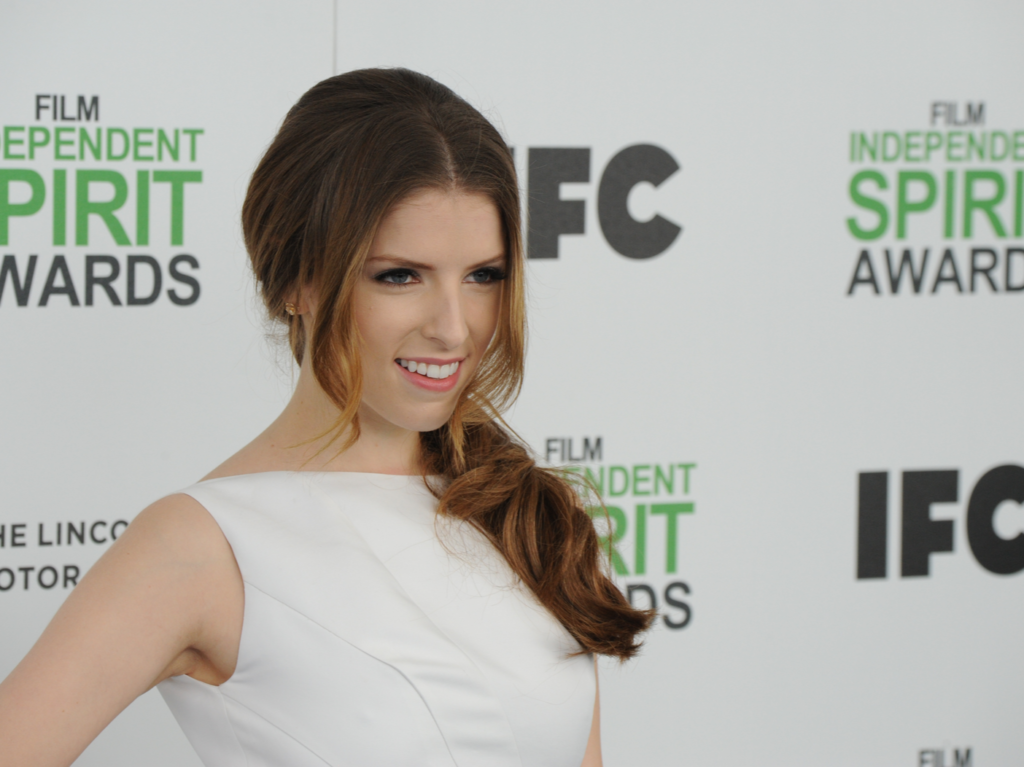 Anna Kendrick in a white top and side pony on the red carpet.