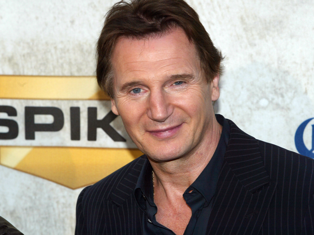 Liam Neeson smiling at the camera wearing a black half-buttoned shirt