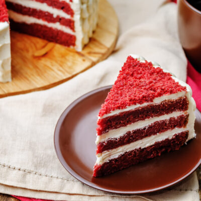 A slice of red velvet cake on a small plate with a mug of coffee and the rest of the cake in the background.