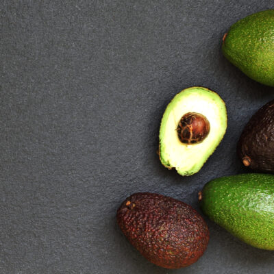 Different varieties of avocados on a dark background.