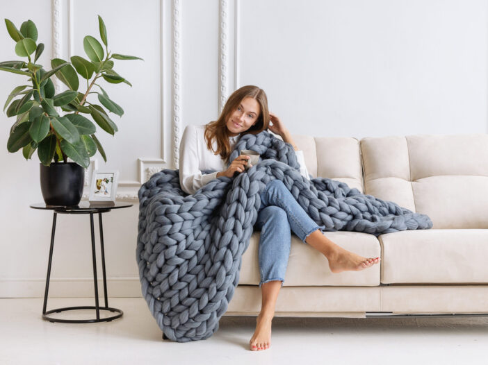 A woman sitting on a cream couch with a chunky gray knitted blanket.