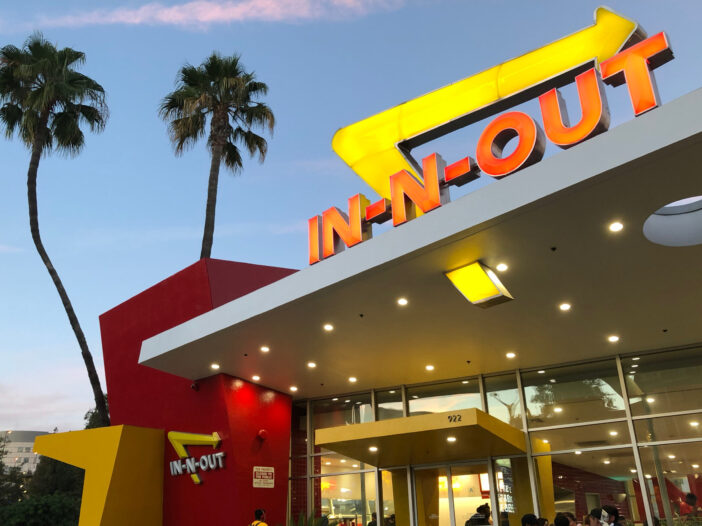 The outside of an In-N-Out restaurant at dusk.