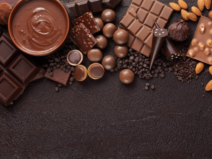 Various types of chocolates on a brown background.