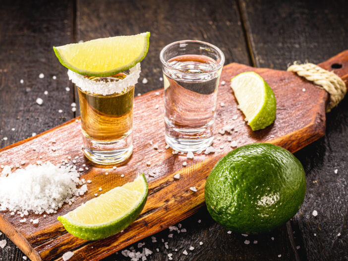Shots of gold and silver tequila on a wooden board with salt and limes.