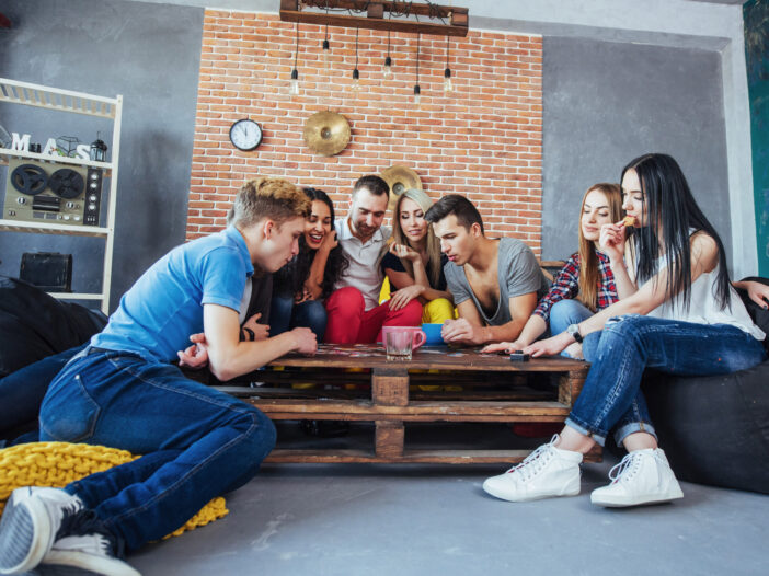Group of friends gathered around a table playing a game.