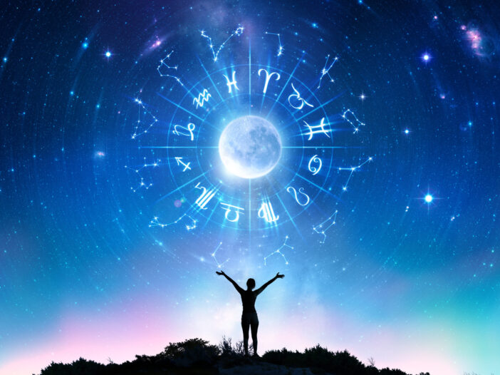 Person with outstretched arms looking at a starry sky with the zodiac signs around a moon.