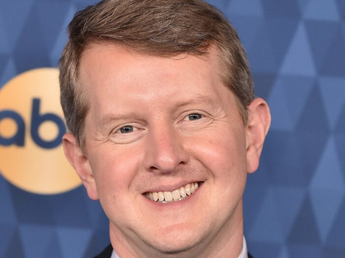 A close up of Ken Jennings' face as he stands against a blue background