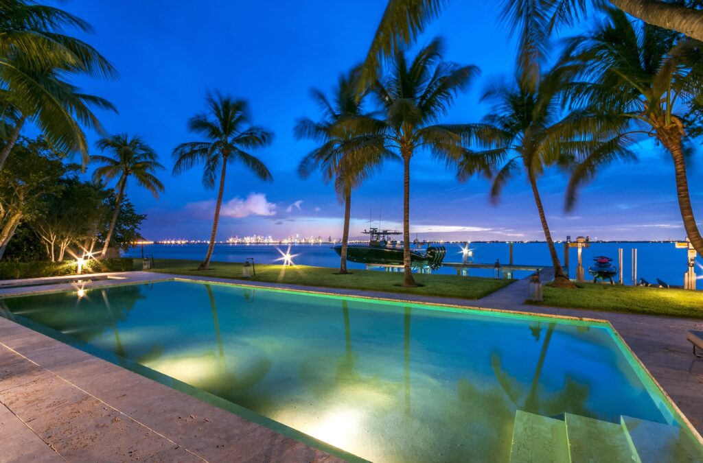 a photo of an outdoor pool facing the water with palm trees