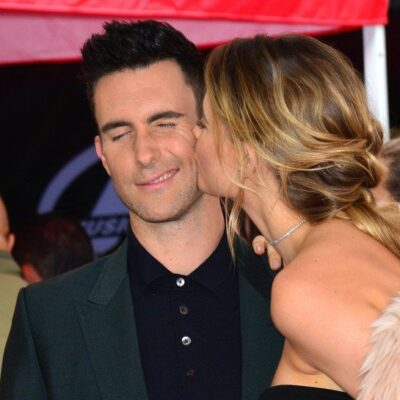 Adam Levine in a suit gets a kiss on the cheek from his wife Behati Prinsloo