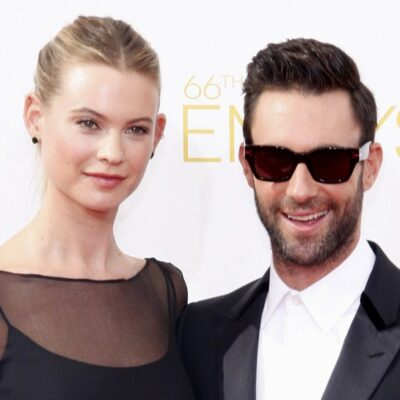 Adam Levine on the right, with his arm around his wife, Behati Prinsloo.