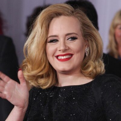 Adele, wearing a black dress, waves to photographers at the Kong Skull Island premiere