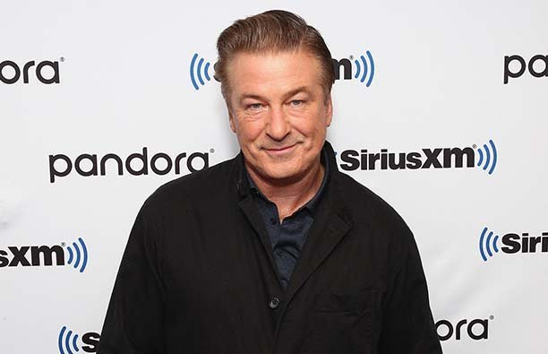 Alec Baldwin in a dark shirt and jacket smiling in front of a SiriusXM background