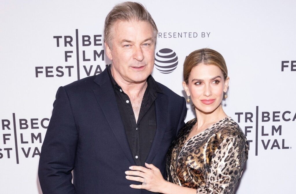 Alec Baldwin in a navy suit standing with wife Hilaria Baldwin in a leopard print dress