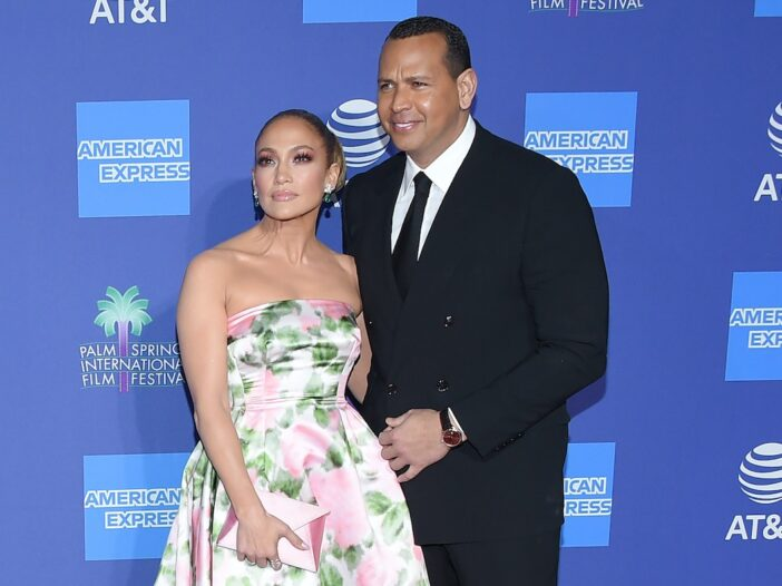 Alex Rodriguez in a suit smiling and posing with fiancee Jennifer Lopez in a floral dress