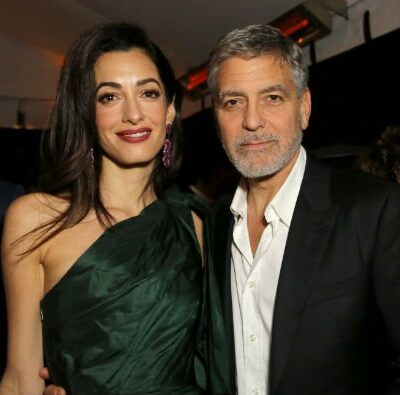 Amal Clooney in a green dress standing near George Clooney in a black suit on the red carpet
