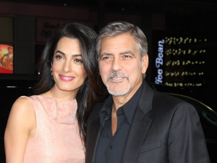 Amal Clooney in a pink dress on the left, George Clooney in a black suit on the right.