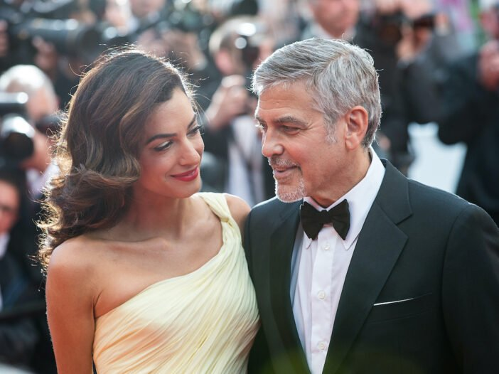 Amal Clooney in a yellow dress smiling at husband George Clooney in a tuxedo