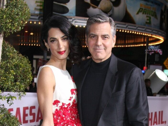 Amal Clooney on the left in a red and white dress, George Clooney on the right in a suit.