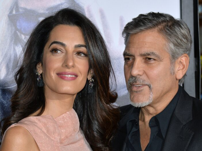 Amal Clooney on the left in a pink dress, George Clooney on the right in a black tux.
