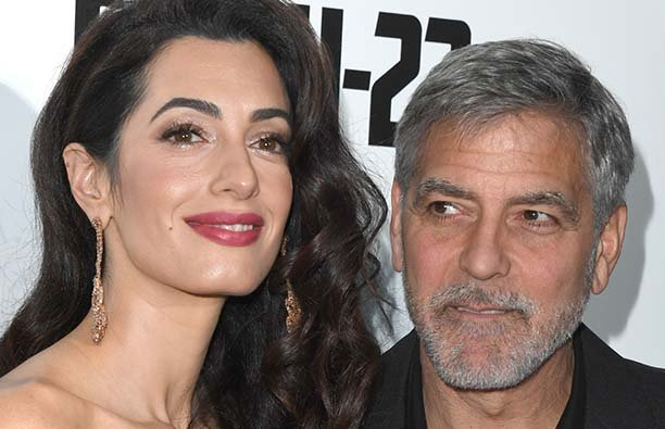 Amal Clooney standing to the right of George Clooney at a red carpet event
