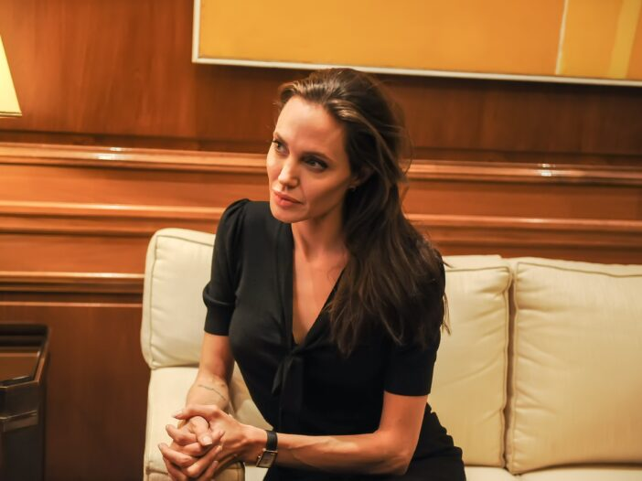 Angelina Jolie in a black outfit, sitting on a cream-colored couch with a serious expression while meeting Alexis Tsipras.