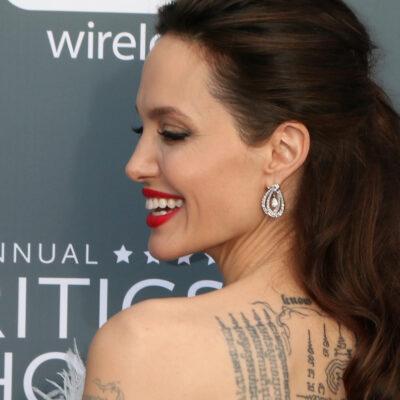 Angelina Jolie looking over her shoulder smiling against a grey background