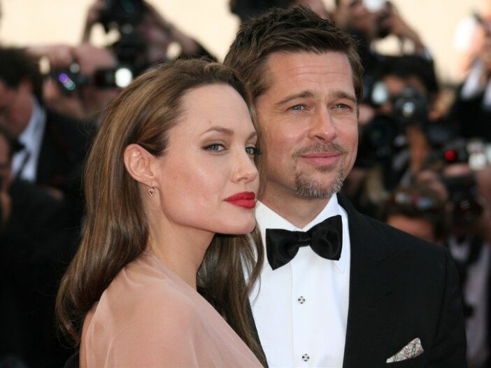 Angelina Jolie on the left, standing with Brad Pitt in formal wear.