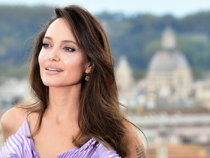Angelina Jolie smiling in a purple dress.