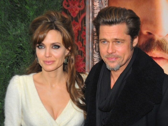 Angelina Jolie, standing next to Brad Pitt, while they were married.