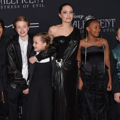 Angelina Jolie standing with her children Pax, Shiloh, Vivienne, Zahara, and Knox on the red carpet