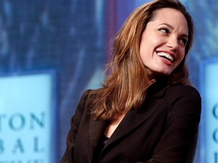 Angelina Jolie turning to the side and laughing.