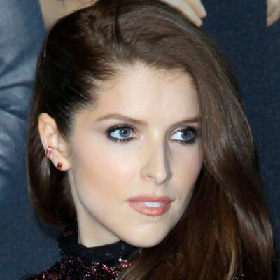 Anna Kendrick wearing a black dress decked out in red gemstones looks over her shoulder.