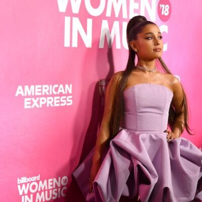 Ariana Grande in a pink dress against a pink background