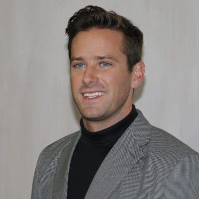 Armie Hammer wears a gray suit jacket over a black shirt against a plain white background
