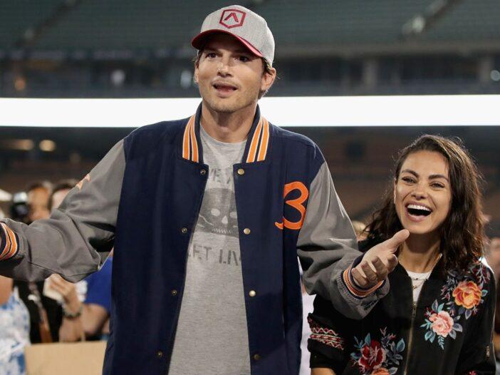 Ashton Kutcher looking bemused as Mila Kunis laughs at something next to him.