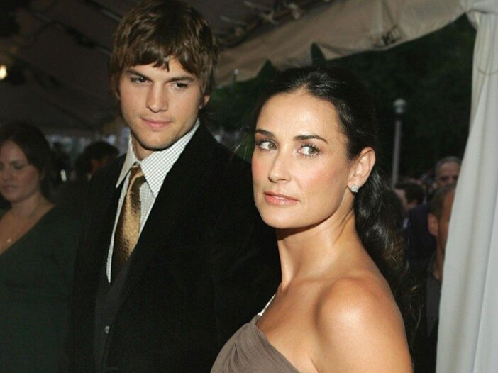 Ashton Kutcher standing behind Demi Moore as both look to the left.
